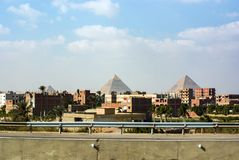 View of the pyramids of Keops, Kefren and Menkaure from the ring road of Cairo. Ahead half-built homes royalty free stock image