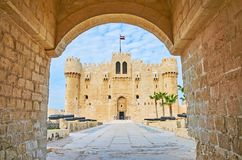The castle through the gate, Alexandria, Egypt. The view on the Qaitbay Fort through its entrance stone gate, the alley with cannons is seen on foreground royalty free stock photo