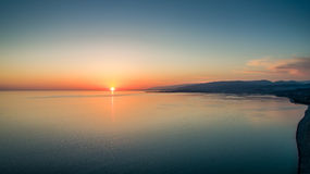 View from the quadrocopter to the bright sunset over the sea. View from the quadrocopter to a bright sunset over a calm sea Royalty Free Stock Photos