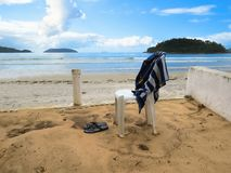 View of deserted beach with chair and towel. View of the quiet and deserted beach in sunny day, with a chair and a towel Royalty Free Stock Images