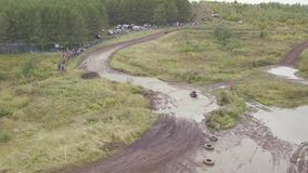 View of race track on quad bikes. Clip. Top view of quad bikes passing puddles of mud at races. Cross-country motorcycle. Racing stock footage