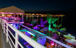 View through the railing and waterfront cafes at night shore with a beach and umbrellas and highlighted with bright. Colors, Crete, Greece Stock Images
