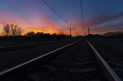 View of railroad going straight away to sun. Dark silhouettes railway infrastructure against background of dramatic sunset. View of railroad going straight away stock photography
