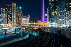 View of railroad tracks and modern buildings in downtown at nigh Stock Photos