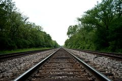 View of the railroad tracks with trees Stock Photo