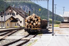 A view of railroad and wood carrying train in the alps switzerland.  Stock Photos