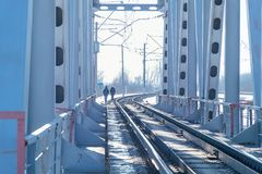 View of the railway bridge from the inside. At the end of the bridge, you can see two people walking Royalty Free Stock Image