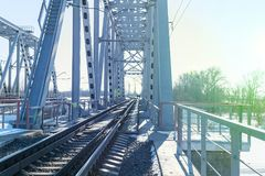 View of the railway bridge from the inside. At the end of the bridge, you can see two people walking Stock Image