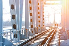 View of the railway bridge from the inside. At the end of the bridge, you can see two people walking in the sun Royalty Free Stock Image