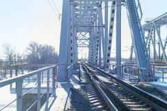 View of the railway bridge from the inside. At the end of the bridge, you can see two people walking Stock Photos