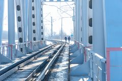 View of the railway bridge from the inside. At the end of the bridge, you can see two people walking Stock Images