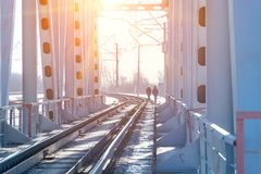 View of the railway bridge from the inside. At the end of the bridge, you can see two people walking in the sun Stock Image