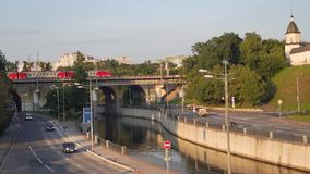 View of the railway bridge over the Yauza river and roadway of its embankment in sunset light, Moscow. stock footage