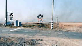 View of the railway crossing with flashing traffic lights, day. Ukraine stock footage