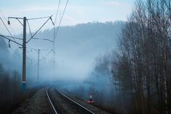 View of railway and electric poles in fog in spring royalty free stock photo