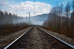 View of railway and electric poles in fog in springtime. View of railway and electric poles in fog in morning springtime royalty free stock images