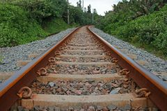 Railway tracks curving in the distance. View of railway line, sleepers and gravel in coastal region, lined by green vegetation royalty free stock photography