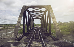 View of railway and old steel bridge with green tree at the left and right side of railway,blue sky and clouds on background royalty free stock images