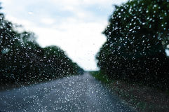 A view of the rainy weather through the windshield of a car that rides along the road. Stock Photos