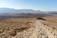 Trekking in Negev dramatic stone desert, Israel. View of ramon crater desert of southern israel during hiking Royalty Free Stock Photography