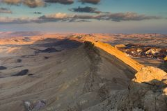 Trekking in Negev dramatic stone desert, Israel. View of ramon crater desert of southern israel during hiking Royalty Free Stock Photo
