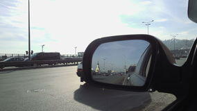 View in rear view mirror of city street traffic stock footage