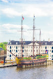 View of a rebuilt Indiaman ship and the Maritime museum in the Amsterdam Harbour Royalty Free Stock Photo