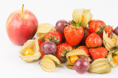 View of red apple with orange physalis, purple grapes and red strawberries. Royalty Free Stock Photo