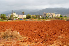 View of red arable land, Malia town and mountain. Royalty Free Stock Images