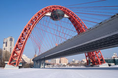 View of red arc bridge on frozen river and houses. View of red arc bridge on frozen Moskva-river and many buildings Royalty Free Stock Image