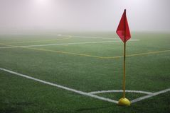 The view from the red corner flag on a football field in fog Stock Photo
