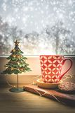 View of a red coffee cup and Christmas decoration on a window with snowy background royalty free stock photos