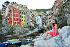 View of red dressed girl sitting on the stones like a mermaid taking photo with mirrorless camera of Italian Riviera landscap Stock Photos