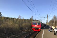 View of a red electric train of Russian Railways approaching the platform in the suburbs stock photos