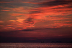 View of red fleecy clouds before sunrise sea on foreground Royalty Free Stock Photos
