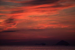 View of red fleecy clouds before sunrise sea on foreground Stock Image