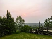 A view of the red sun through smoky hazy orange and brown sky in a park downtown Edmonton, Alberta, Canada. Due to the ongoing forest fires stock photography