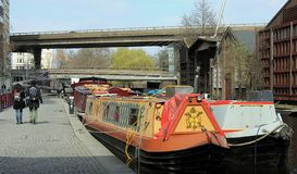 View of the regent canal with houseboats, locals, and visitors in London, England. LONDON UK - APRIL 3 2016: View of the regent canal with houseboats, locals stock photography