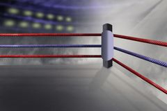 View of a regular boxing ring surrounded by red and purple ropes spotlit. By a spotlight Stock Images