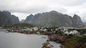 View of Reine. Reine traditional fishing village with rorbu - wooden cabins and characteristic rock behind it, Lofoten peninsula, Norway Stock Photos