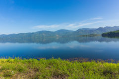 View of reservoir blue sky and green grass royalty free stock photos