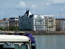 View of residential Buildings on Pest Side from Buda side in Budapest. With tour bus hood in the foreground, the Danube and blue sky above royalty free stock image