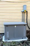 Residential Generator. View of a Residential generator on concrete pad, next to a house wall Stock Photography