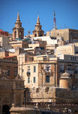 The view of the residential houses of Valletta with two Bell Tow. Ers of Collegiate Parish Church of St Paul's Shipwreck on the background, Malta Royalty Free Stock Photos