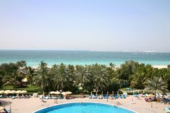 View from resort along coast in Dubai. With pool and palm trees Stock Image