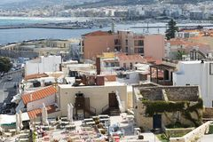 View of resort Greek architecture Rethymno city-port, built by Venetians, from height of Fortezza Castle - fortress on hill Paleok. Astro. Red tiled roofs and Stock Images