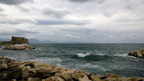 View of the restless Gulf of Naples with a great-looking wave and a castle Castel Dell`ovo Stock Photo