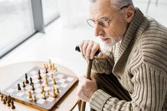 View of retired man in glasses thinking while sitting near chess board at home