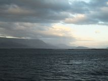 View from the Reykjavík Harbour; hills and cloudy sky royalty free stock photos