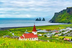 View of Reyniskirkja Church in Vik of Iceland. With beautiful yellow flowers field in the foreground and Reynisdrangar rock formation in the background stock images